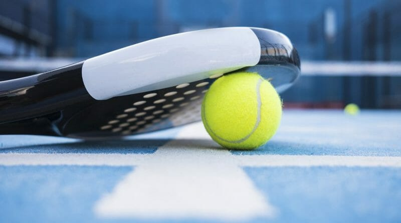 Tennis racquet on blue court
